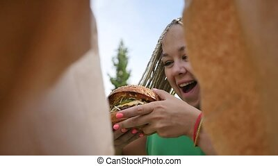 Pretty young woman is eating appetizing hamburger on the ...