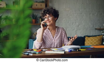 Pretty young woman is glasses is talking on mobile phone and smiling sitting at desk with stationery at home. Communication, houses and technology concept.