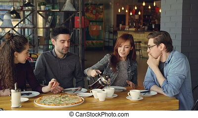 Pretty young woman is pouring tea in cups from teapot and...