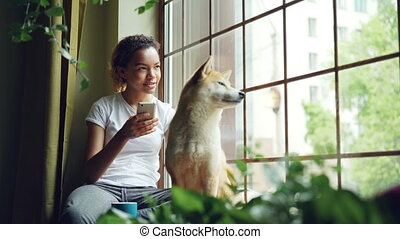 Pretty young woman is sitting on window sill and using...