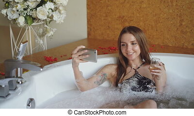 Pretty young woman is taking selfie with champagne glass...