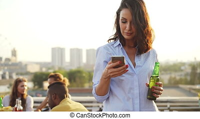 Pretty young woman is using smartphone, holding bottle and smiling during rooftop party with big city in background. Modern lifestyle and technology concept.