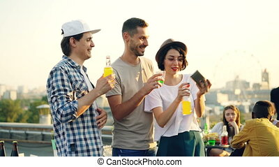 Pretty young woman is using smartphone to take selfie with her cheerful male friends, young people are posing then laughing and watching funny photos.