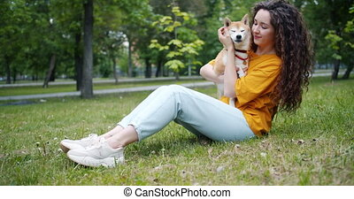 Pretty young woman kissing dog's muzzle and smiling sitting...