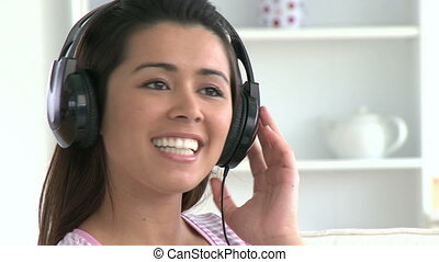 pretty young woman listen to music sitting on the couch...