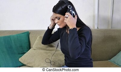 Pretty young woman listening to music with headphones