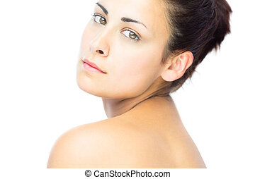 Pretty young woman looking over shoulder at camera