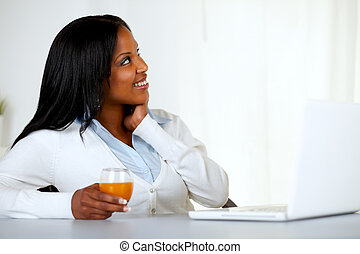 Pretty young woman looking up with an orange juice