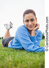 Pretty young woman lying on the grass