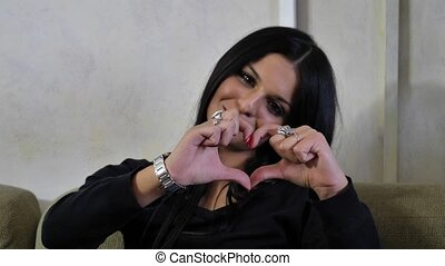 Pretty young woman making heart sign with hands
