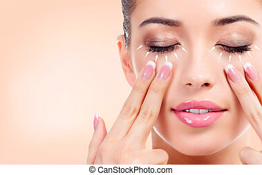 Pretty young woman massaging her face. Antiaging concept