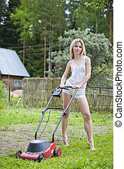 Pretty young woman mowing the grass.