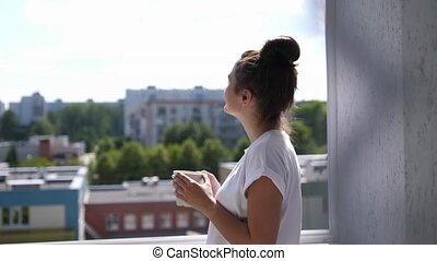 Pretty young woman on balcony looking out over city drinking a cup of tea or coffee