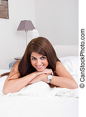 pretty young woman on the bed smiling