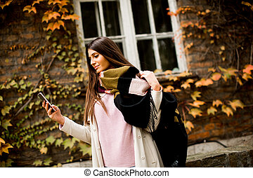 Pretty young woman on the city street with mobile phone