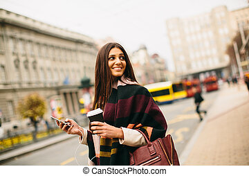 Pretty young woman on the street at autumn day