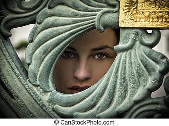 Pretty young woman peeking through hole in metal gate