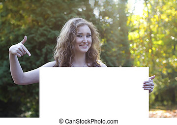 pretty young woman points to a billboard