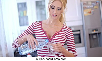 Pretty young woman pouring bottled water