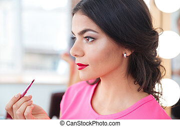 Pretty young woman putting on red lipstick