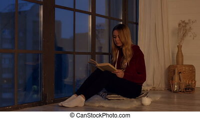 Pretty young woman reading book by window at home