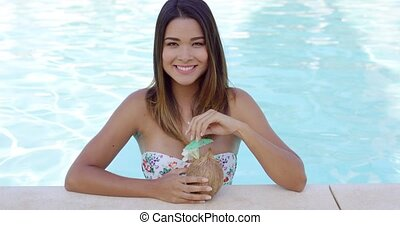 Pretty young woman relaxing in a resort pool