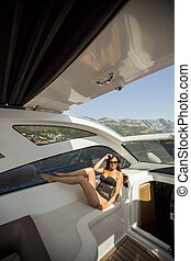 Pretty young woman relaxing on the yacht at sunny day