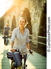 Pretty, young woman riding a bicycle in a city