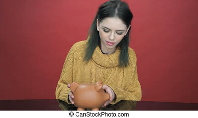 Pretty young woman shaking her piggy bank