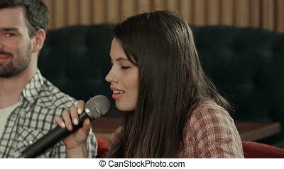 Pretty young woman singing karaoke. Close up. Professional...