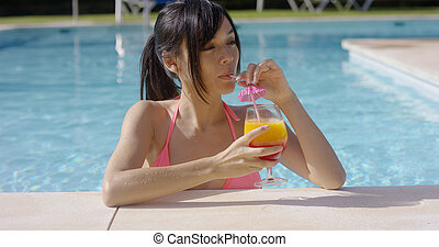 Pretty young woman sipping a cocktail in  pool