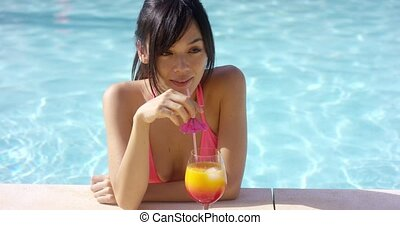 Pretty young woman sipping a tropical cocktail