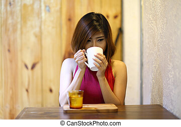 pretty young woman sitting in the cafe and drink coffee