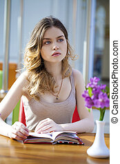 Pretty young woman sitting in the cafe