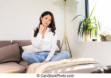 Pretty young woman sitting on a couch