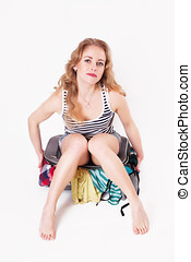Pretty young woman sitting on a suitcase