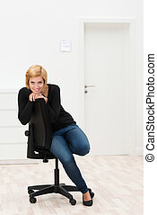 Pretty Young Woman Sitting on Chair at Office