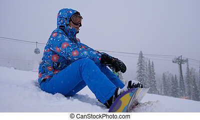 Pretty young woman sitting on mountain peak with her snowboard and enjoying weather during snowfall. Young woman on ski slope