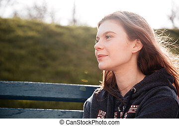 Pretty young woman sitting on the bench in park