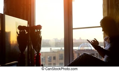 Pretty young woman sitting on window uses smart phone on background of the sunset and city.