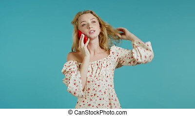 Pretty young woman speaks serious on mobile phone. Beautiful girl holding and using smart phone. Floral outfit. Blue studio background