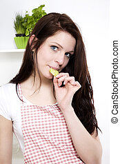 pretty young woman standing in her kitchen  nibbling on a fresh cucumber