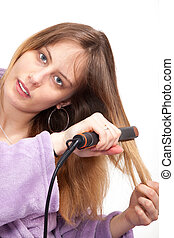 pretty young woman straightening her hair with white background