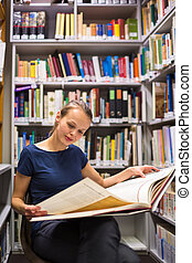 Pretty, young woman studying an old book in archives