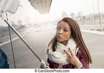 pretty young woman takes a selfie outdoor