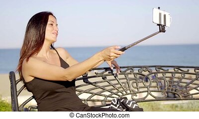 Pretty young woman taking a selfie on her mobile