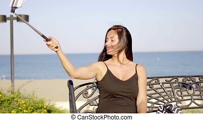 Pretty young woman taking a selfie on her mobile using a...
