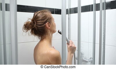 Pretty, young woman taking a shower