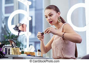 Pretty young woman testing cosmetics on camera