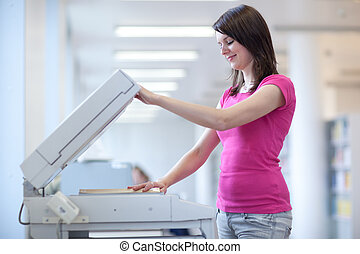 pretty young woman using a copy machine (shallow DOF; color...